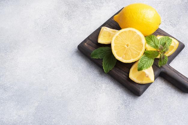 Limões amarelos suculentos inteiros e cortados com folhas de hortelã fresca