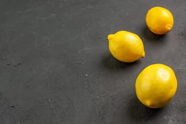 Limões azedos frescos alinhados em uma mesa escura com limão cítrico amarelo