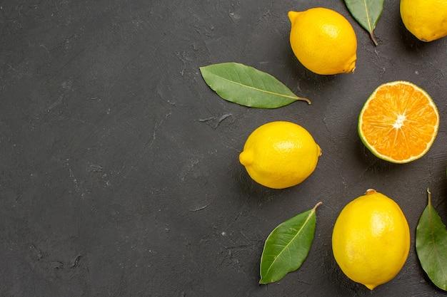 Limões azedos frescos alinhados em uma mesa escura com limão cítrico e frutas amarelas