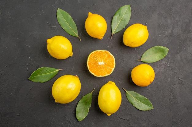 Limões azedos frescos alinhados em uma mesa escura de limão cítrico amarelo