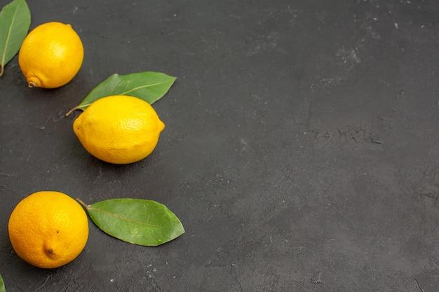 Limões azedos frescos alinhados em uma mesa escura de limão citrino amarelo