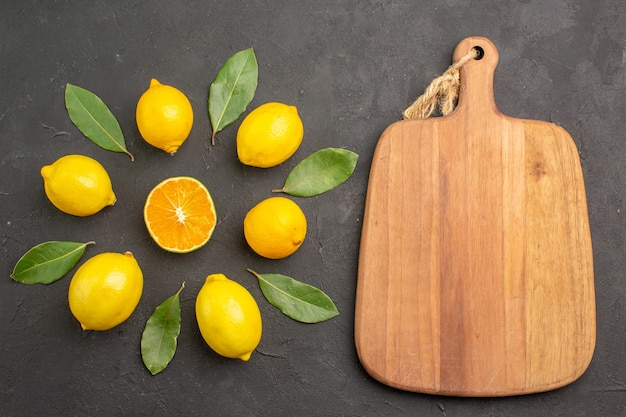 Limões azedos frescos alinhados na mesa escura com frutas cítricas amarelas