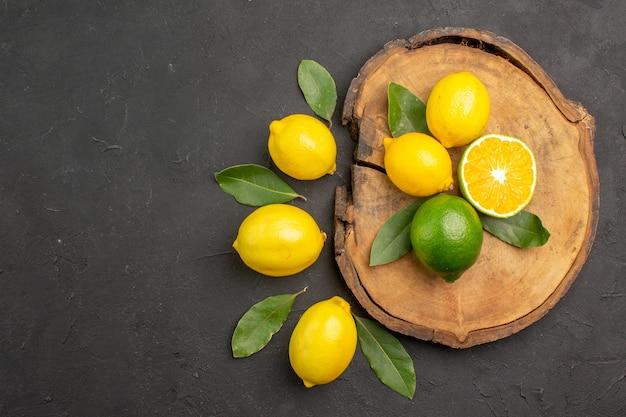 Limões azedos frescos com folhas no chão escuro, frutas e limão amarelo cítrico