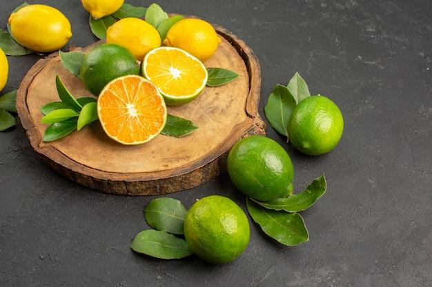 Limões azedos frescos de vista frontal em fundo escuro
