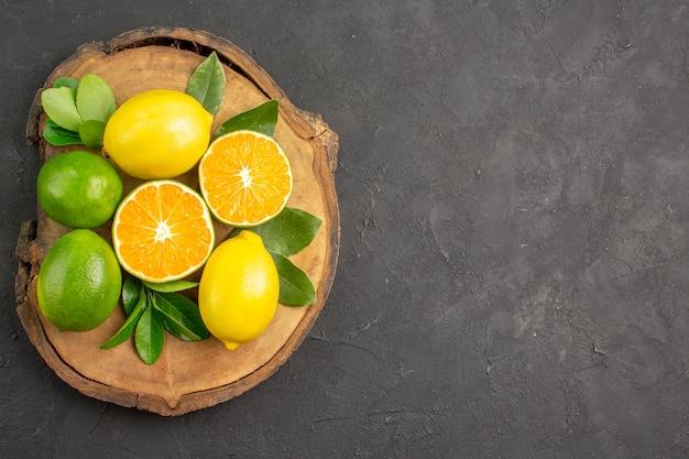Limões azedos frescos na mesa escura de lima cítrica vista de cima