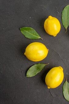 Limões azedos frescos revestidos em piso escuro com limão cítrico amarelo lima