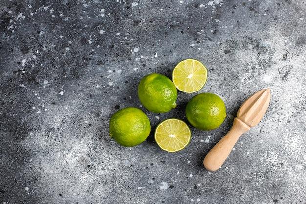Limões-chave frescos com espremedor de citrinos de madeira, vista superior