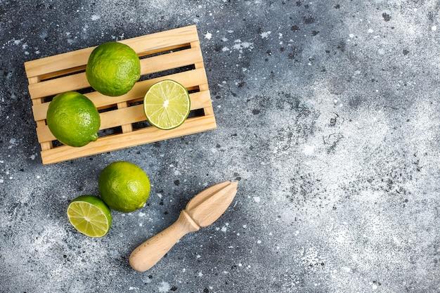 Limões-chave frescos com espremedor de citrinos de madeira
