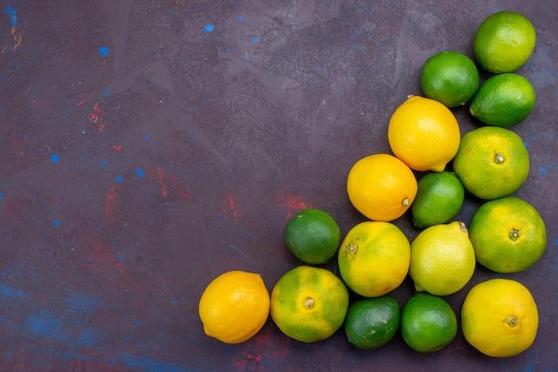 Limões cítricos suculentos e tangerinas alinhadas em uma mesa escura com frutas cítricas tropicais exóticas de laranja