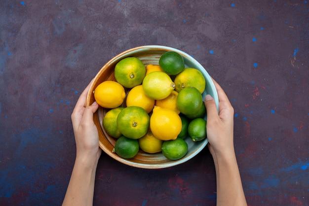 Limões cítricos suculentos e tangerinas em uma mesa escura de frutas cítricas tropicais exóticas