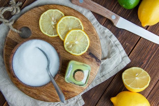 Limões com bebida, tábua, sal, faca plana leigos na toalha de madeira e cozinha
