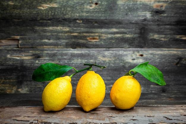Limões com e sem folhas vista lateral sobre um fundo escuro de madeira