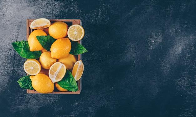Limões com fatias e folhas em uma caixa de madeira no fundo textured preto, vista superior. copie o espaço para texto