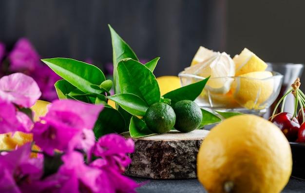 Limões com fatias, flores, tábua de madeira, cerejas close-up sobre uma superfície cinza