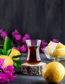 Limões com fatias, flores, tábua de madeira, copo de chá vista lateral na superfície cinza e grunge