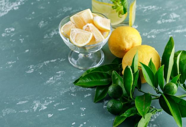 Limões com fatias, folhas, água de desintoxicação na superfície de gesso