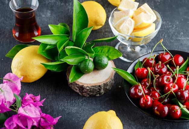 Limões com fatias, folhas, copo de chá, flores, cerejas, placa de madeira na superfície cinza