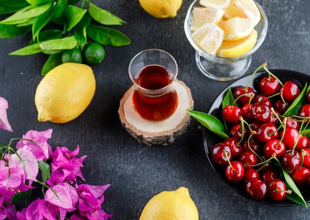 Limões com fatias, folhas, flores e copo de chá