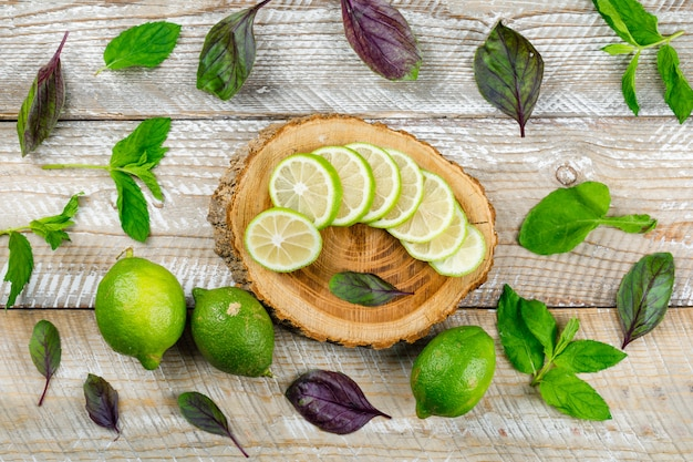 Limões com folhas de manjericão na tábua de madeira e corte, plana leigos.