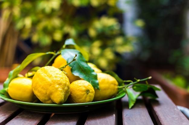 Limões com folhas em uma tigela verde sobre uma mesa de madeira.