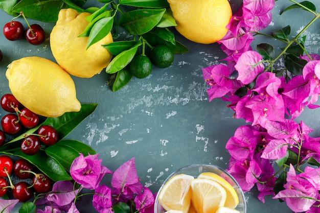 Limões com folhas, fatias, flores, cerejas na superfície de gesso