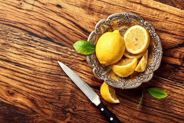 Limões com folhas na mesa de madeira de carvalho. copie o espaço para design ou texto. vista superior de frutas com faca.