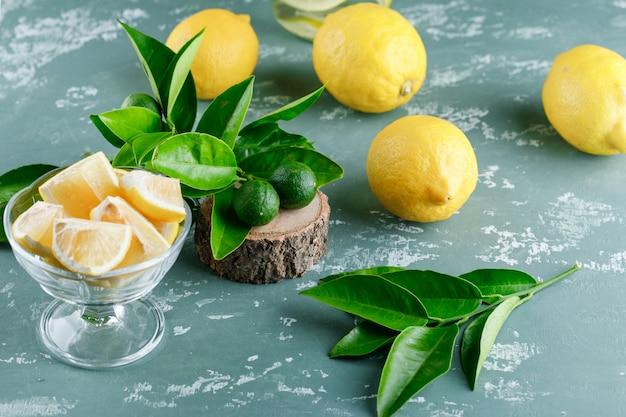 Limões com folhas, vista de alto ângulo de tábua de madeira em uma superfície de gesso