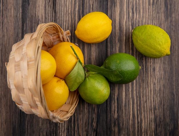 Limões com limas em uma cesta invertida em fundo de madeira.
