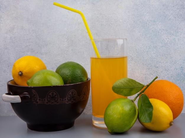 Limões com limas em uma panela com um copo de suco de laranja em um fundo cinza
