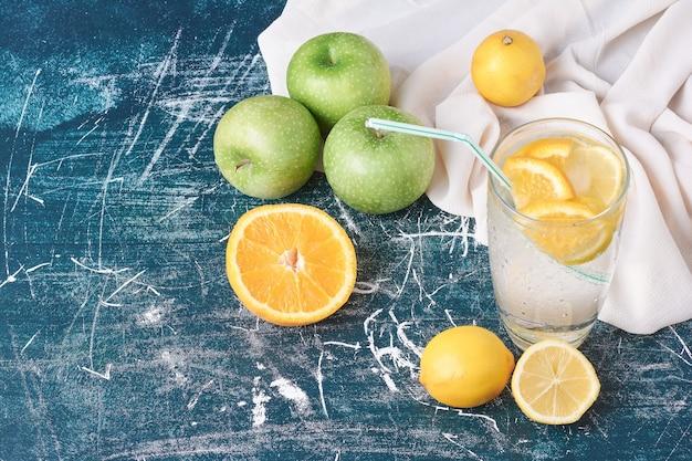 Limões com um copo de bebida em azul.