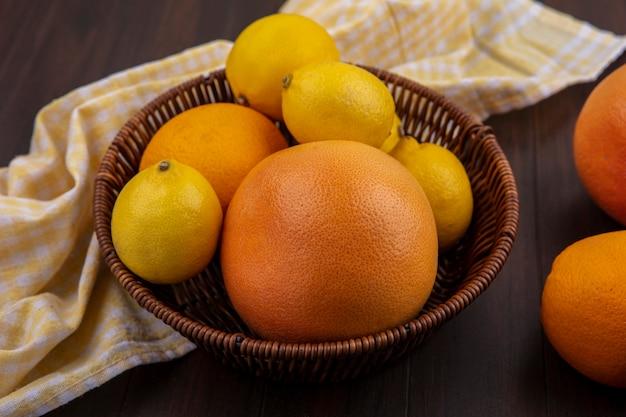 Limões de vista frontal com laranja e toranja em uma cesta com toalha amarela quadriculada em fundo de madeira