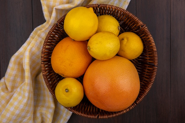 Limões de vista superior com laranja e toranja em uma cesta com toalha amarela quadriculada em fundo de madeira
