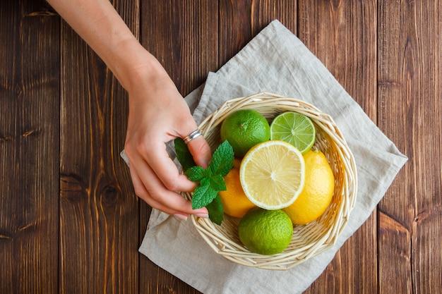 Limões de vista superior na cesta com a mão segurando as folhas de limão na superfície de madeira.