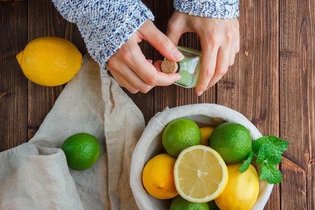 Limões de vista superior na cesta com um pano branco, as mãos segurando uma garrafa de suco de limão na superfície de madeira. vertical