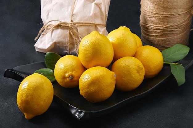 Limões dispostos em um prato escuro, uma bela composição de limões. frutas frescas, entrega de mercearia.