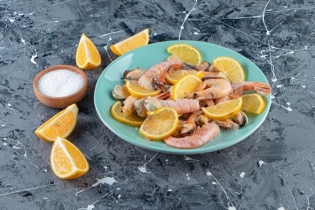 Limões e camarões fatiados em um prato ao lado de uma tigela de sal, na superfície de mármore.