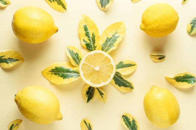 Limões e folhas verdes isoladas em amarelo