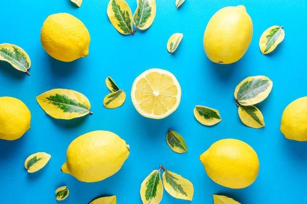 Limões e folhas verdes isoladas em azul