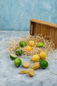 Limões e limas com caixa de madeira sobre superfície de mármore cinza e azul
