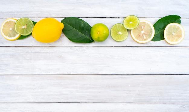 Limões e limas com verde folhas sobre fundo de madeira