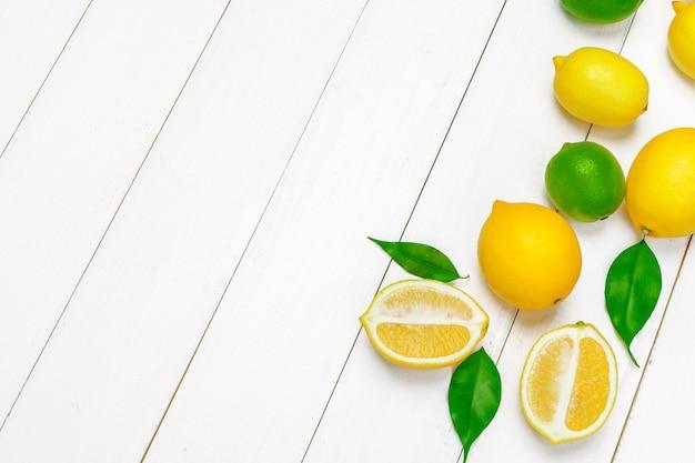 Limões e limas em um fundo branco de madeira.