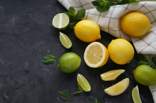 Limões e limas em um fundo escuro, vista superior