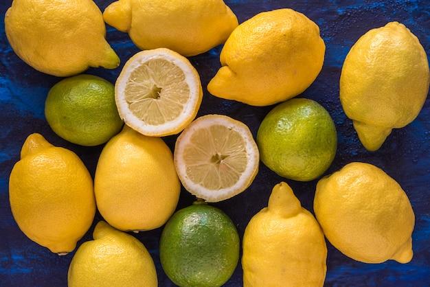 Limões e limas em uma tabela com texturas azuis