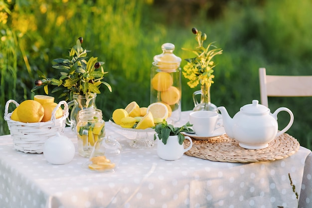 Limões e macaroons amarelos na luz do sol da mesa