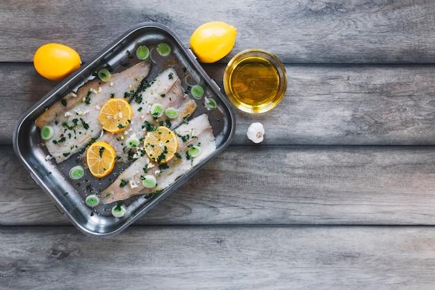 Limões e óleo perto de peixe