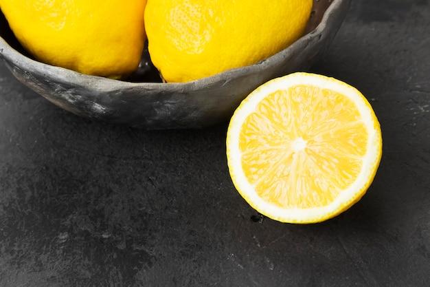 Limões em tigela de barro em um fundo escuro