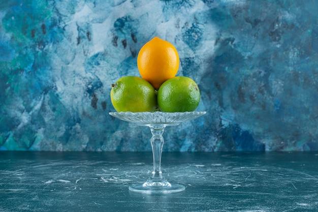 Limões em um pedestal de vidro, na mesa de mármore.