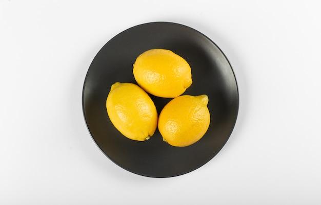 Limões em um pires preto isolado. vista do topo