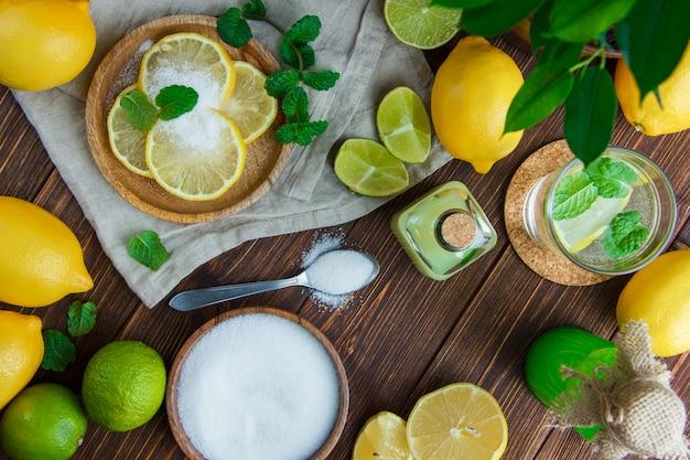 Limões em um prato com bebidas, sal, ervas, limas planas leigos na toalha de madeira e cozinha