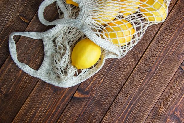 Limões em um saco de malha em uma mesa de madeira. configuração plana.